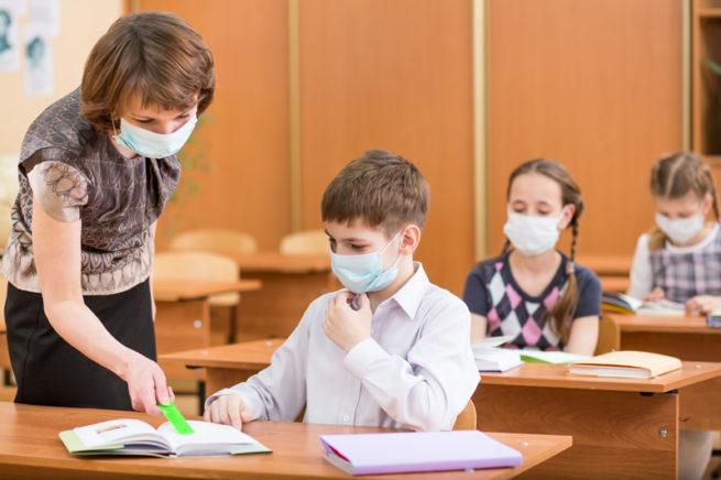 Enseignante et écoliers portant un couvre-visage en classe.